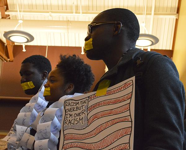 (Left to right) Sophomores Denzel Woodall, Kamille Brashear, Gbadebo Balogun stand during the protest on Dec. 15. Photo by Ryan Silvola.