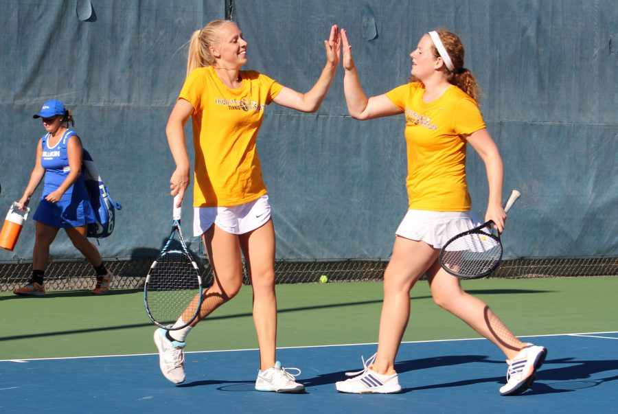 Dana+Goggin+and+Aileen+MacDonald+high+five+at+their+match+against+Milikin+College+Sept.+9.+