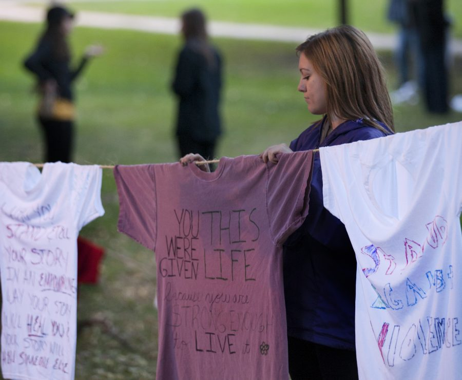 Senior+Lisa+Williams+adjusts+a+t-shirt+on+a+rope+for+Augustana%E2%80%99s+Clothesline+Project+that+was+displayed+in+the+lower+quad.+The+Clothesline+Project+raises+awareness+about+violence+against+women.%0APhoto+by+LuAnna+Gerdemann.