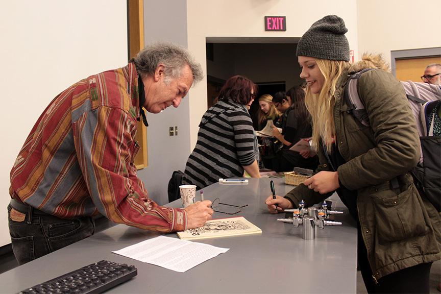 Artist+William+Stout+signs+one+of+his+books+for+senior+Amanda+Ebert.+Photo+by+Lu+Gerdemann.