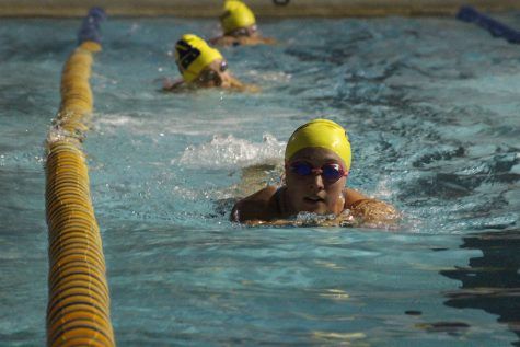 Junior Kristin Schoenecker works through the swim practice during a kick board set. Photo by Kevin Donovan