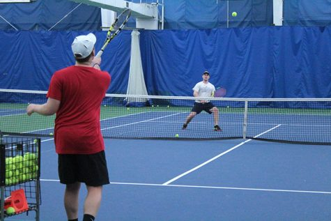 Members of the Men's Tennis team practice a drill at the Moline Tennis Club. Photo by Lu Gerdemann.