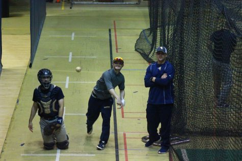 Baseball pitching coach Justin Hauer works with junior Jack Hallmark during practice. The Vikings will play two CCIW teams this weekend. Photo by Tawanda Mberikwazvo.