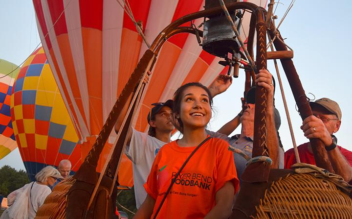 Kyra+Biarkis%2C+senior%2C+climbs+into+the+basket+and+looks+skyward+as+three+pilots+fire+up+the+hot+air+balloons+burners.+Though+the+weather+on+Friday+was+too+unstable+for+visitors+to+float+more+than+a+few+feet+off+the+ground%2C+children+and+adults+still+climbed+into+the+balloon+baskets+to+be+lifted+into+the+air.+Volunteers+were+allowed+to+ride+free+of+charge.%0APhoto+by+Thea+Gonzales