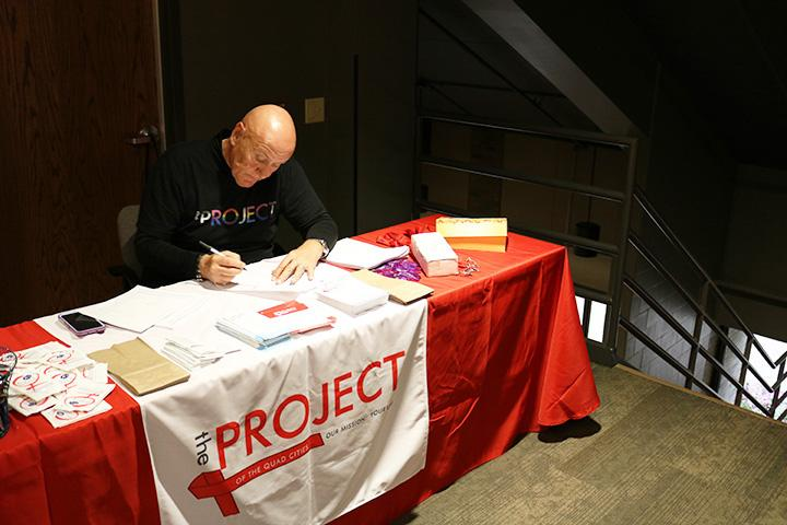 Clyde+Lipp%2C+Program+Manager+at+the+Project+of+the+Quad+Cities%2C+goes+through+paperwork.+Photo+by+Brady+Johnson