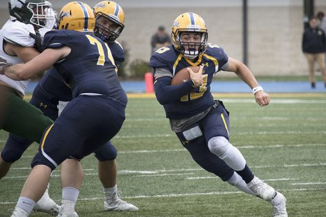 Alek Jacobs, the quarterback for the Augustana Vikings, runs the ball towards the end-zone, as his teammates help keep the Wesleyan Titans from tackling him. The Vikings lost 28-10. Photo by Brady Johnson