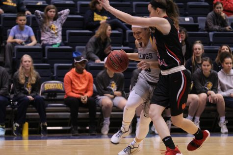 Junior Izzy Anderson pushes past an opponent on her way to the basket. Photo by Tony Dzik