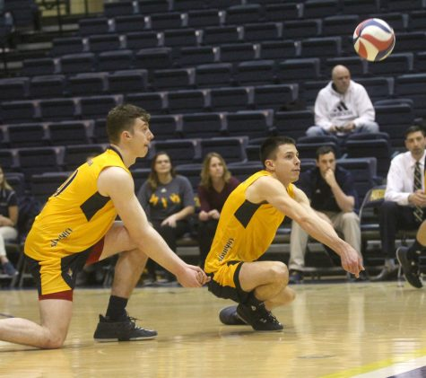 (left to right) Justin Murphy (21) and Dylan Baum (21) kneel to hit the ball during the Vikings match against Mount Mercy on Wednesday night. Photo by Kevin Donovan