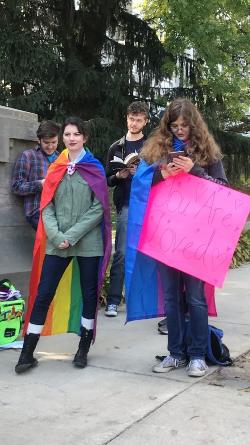 +Sophomore+Naomi+Beckley+and+Senior+Elise+Campbell+protesting+for+GSA+with+flags+draped+across+them.%0A