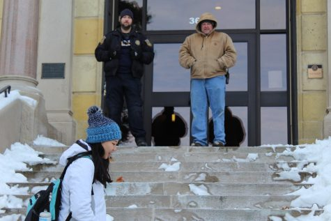 Student Rachael Heah walks past Marcus Masters, first shift Public Safety officer, and Chris Scott from the Instruction Department, who are keeping students from entering Old Main Jan. 21, 2018.