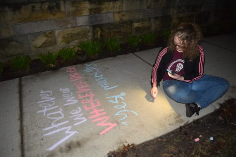 Senior Emma Nordmeyer bends down to write a message in chalk near midnight on Thursday, April 25. Members of the #MakeAChange movement chalked the lower quad, Old Main stairs and 7th avenue sidewalk. Photo by Thea Gonzales.