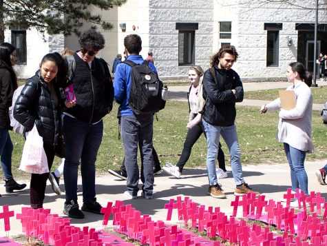 Students gather to look at the pink crosses in the pro-life clubs display on Monday, April 1. Each of the 911 crosses signifies an abortion performed at Planned Parenthood each day. Photo by Emily Jacobson.