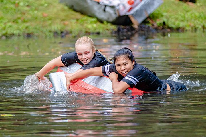 Augustana sophomores Lianna Ubungen (front) and Alexandria Roggensack (back) of the Chi Omega Gamma Sorority race through the Slough at the Cardboard Regatta Race during Augustana College's 99th Homecoming on October 1st, 2019.