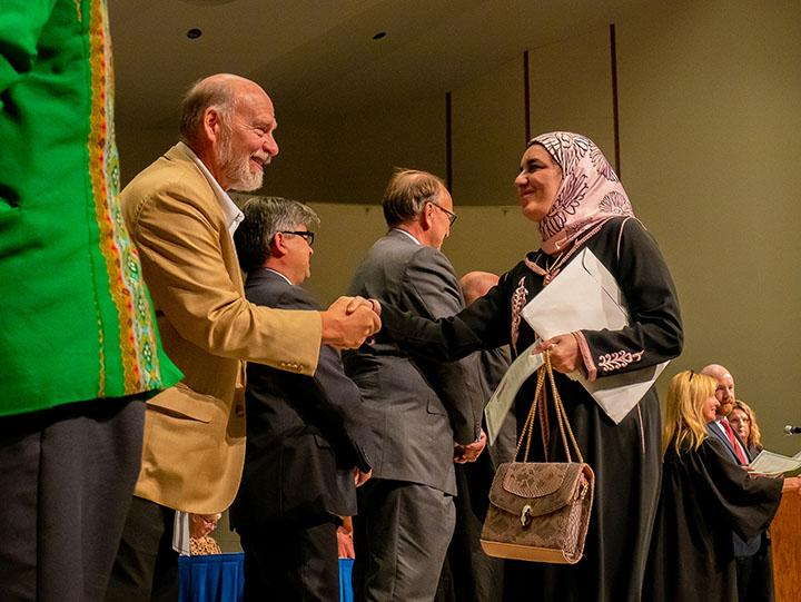 New citizens receive their naturalization certificates and shake hands with the court officials at the naturalization ceremony in Augustana College on October 18, 2019.