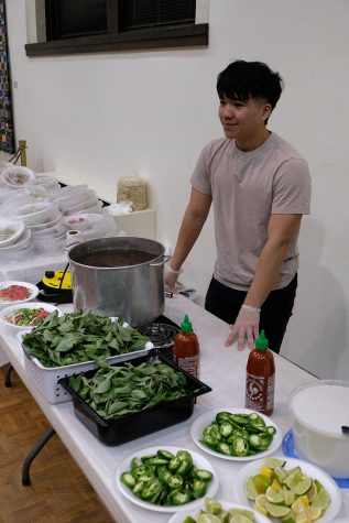 Sophomore Long Nguyen helps staff the Pho-Tastic event in Wallenburg Hall on Saturday night.