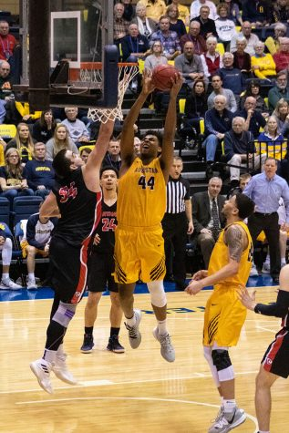 Augustana College senior Micah Martin (#44, right) reaches the ball toward the basket for a dunk on Carthage College senior Brad Perry (#54, left) at the Carver P.E. Center, February 15, 2020.  The Augustana Vikings won the game against the Carthage Red Men with a score of 83 - 81.