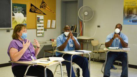 Professor Sharon Varallo, left, teaches the class as Brandon Johnson, center, and Tyrone Stone, right, listen attentively on Oct. 1, 2021.